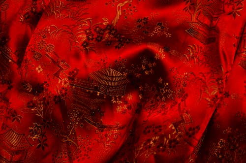 Background of bright fabric with authentic oriental ornaments of floral patterns and traditional huts on creased surface of red textile