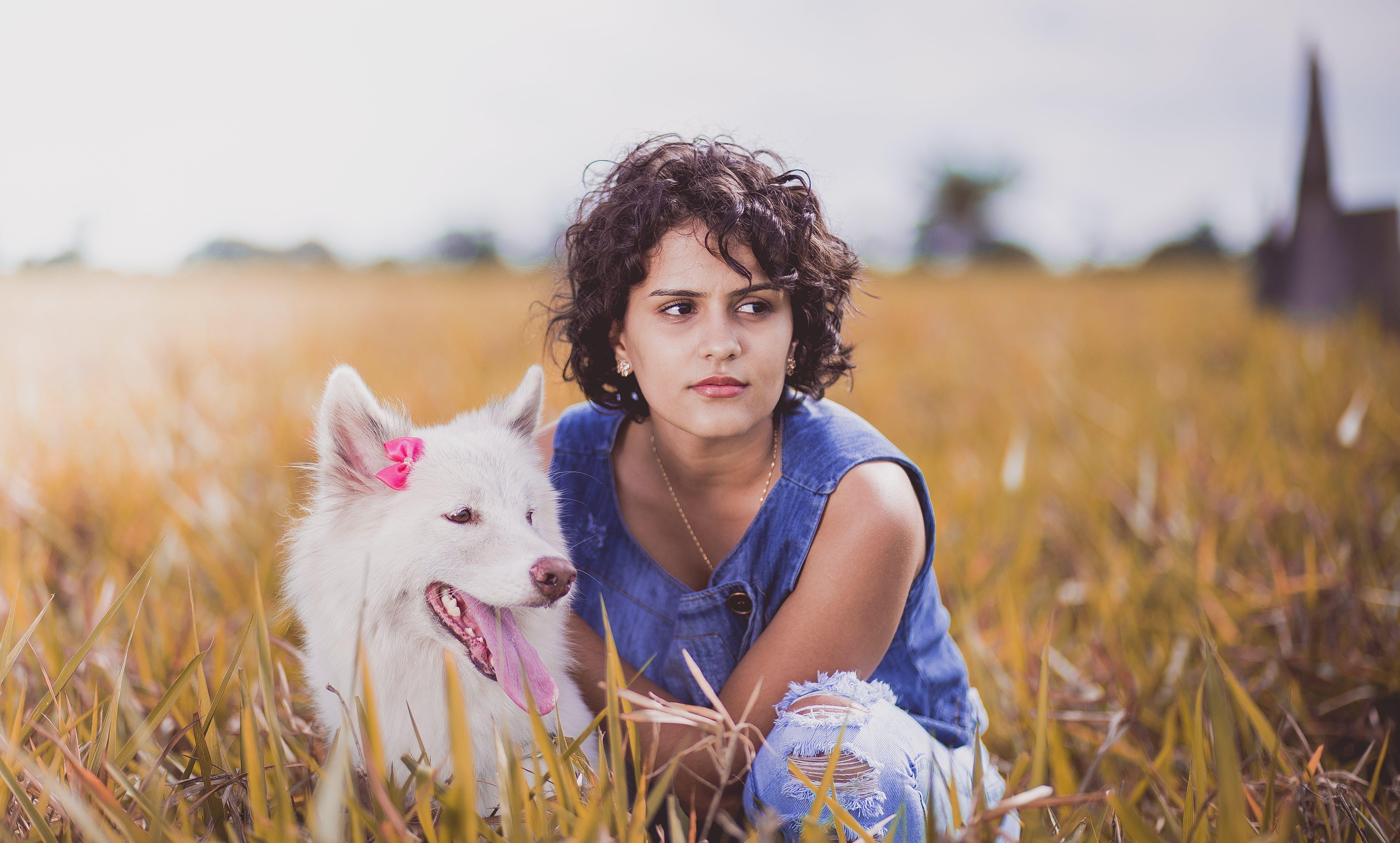 Woman Squatting Near White Dog on Grass Field