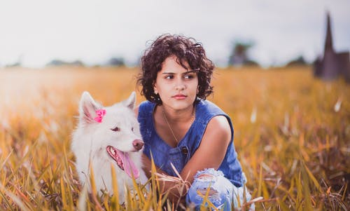 Woman Squatting Near White Dog on Grass Field