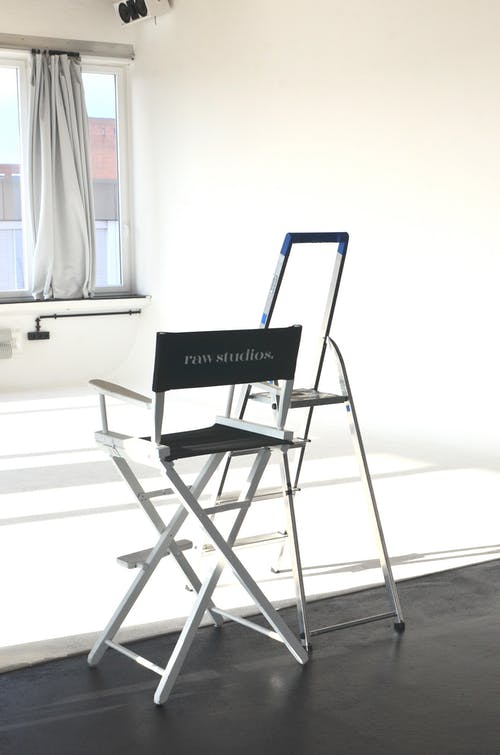 Director chair with inscription and ladder placed in spacious empty studio against big window with curtain in room with white wall