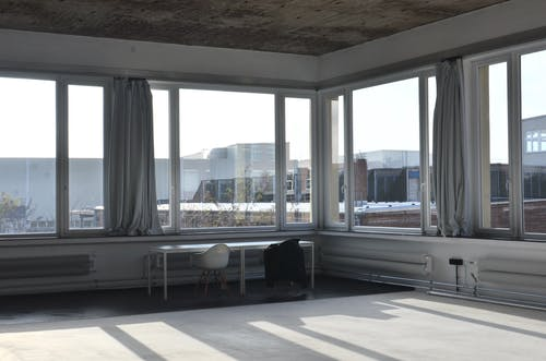 Chairs placed at table near big window with curtain and modern cityscape view with buildings in minimalistic empty room in sunlight