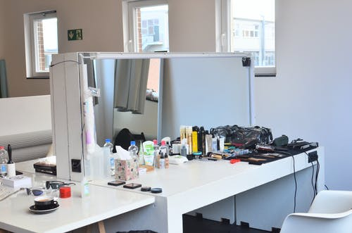 White dressing table with cosmetic products and instruments near table with coffee placed in light room with windows and mattress