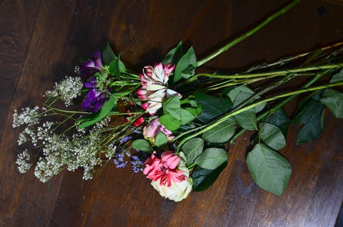 Various flowers on wooden surface