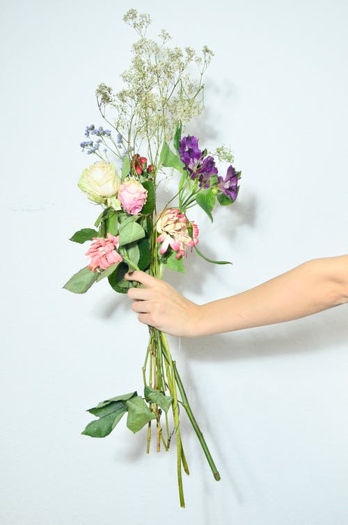 Unrecognizable person demonstrating bouquet of delicate roses gypsophila and purple alstroemeria flowers on green stems on white background in studio