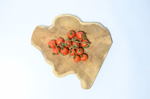 Top view of fresh heap of red cherry tomatoes on green branch placed on shaped wooden board on white background