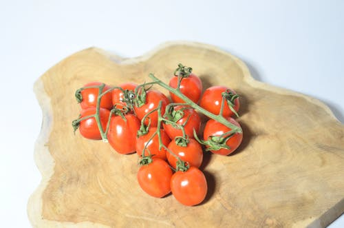 Tomatoes on branch placed on wooden board