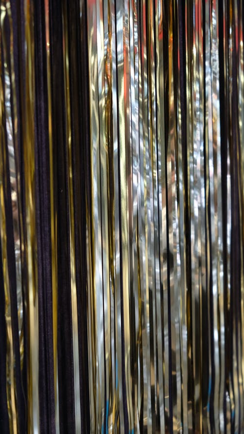Bright shiny silver smooth tinsel hanging straight in rows for decoration during New Year holidays