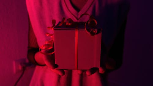 Anonymous female in casual clothes standing with gift box in hands in room illuminated by neon light