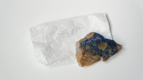 From above of multicolored stone Azurite placed on small sheet of paper with inscription on  white table