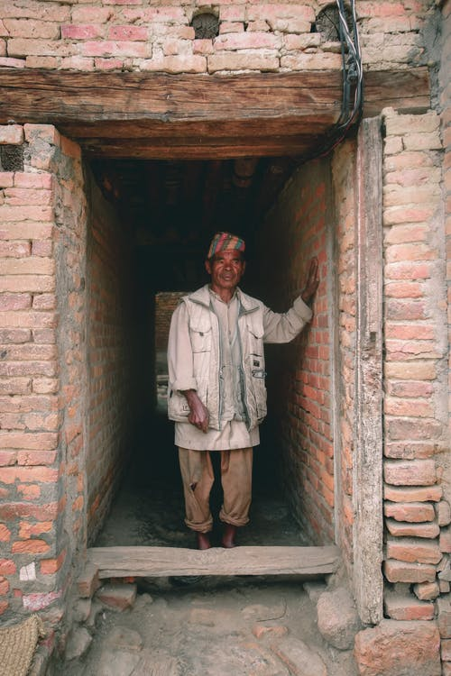 Poor mature ethnic male in traditional clothes touching rough brick wall of construction while looking away