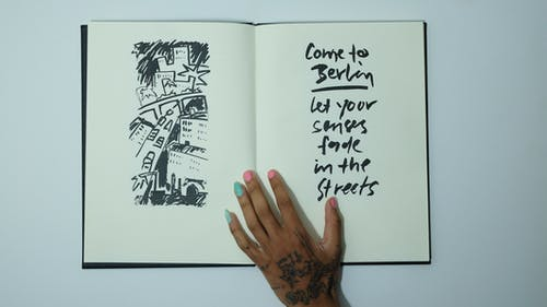 Unrecognizable woman with opened sketchbook with inscription and drawing