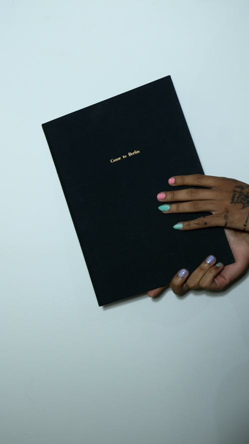Crop anonymous informal female with tattoos and colorful manicure demonstrating book with black cover against gray background