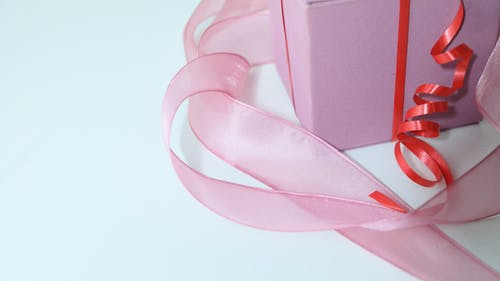 From above of pink cardboard present box decorated with colorful ribbons on gray background