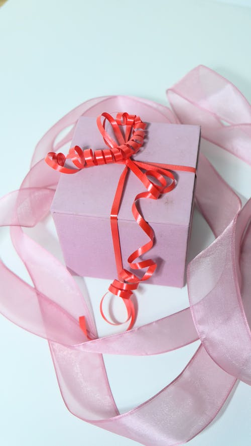 From above of pink cardboard present box tied with red band bow and ribbon on gray background