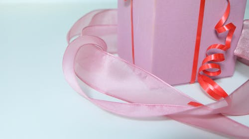 High angle of pink gift box tied with red band and decorated with ribbon on gray background