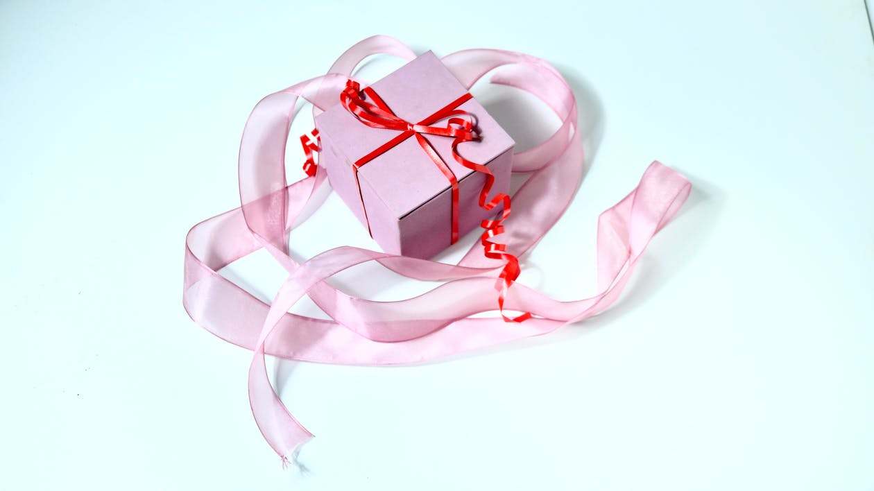 Present box decorated with red band and ribbon