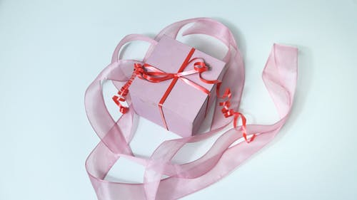 From above of pink cardboard gift box tied with red band and decorated with ribbon on gray background