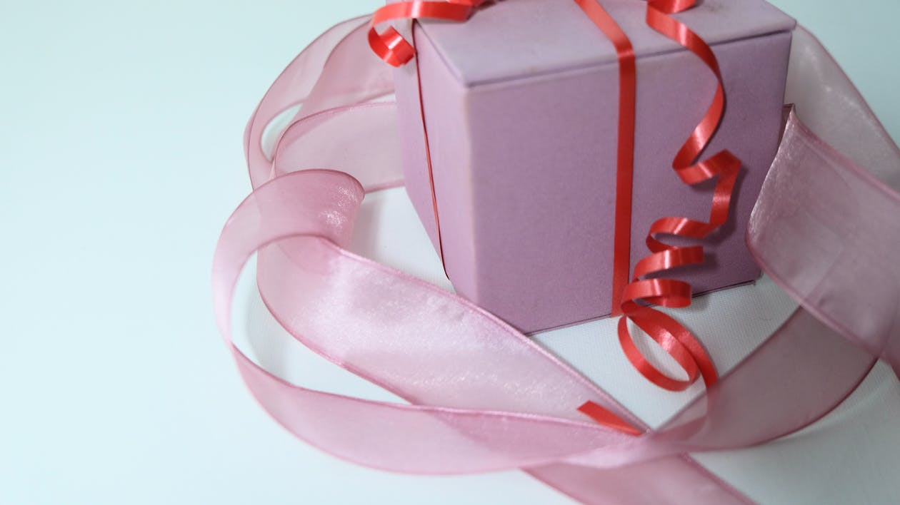 From above of pink carton present box decorated with ribbon and tied with red band on gray background