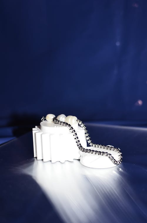 Small white earring with thin metal chain placed on white detail on table in dark room