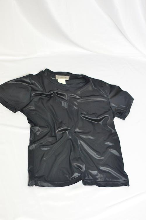 Black shiny t shirt with short sleeves against white background