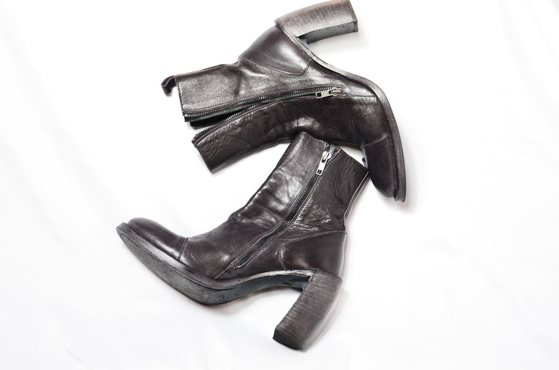 Top view of pair of dark brown leather boots with zipper and wide high heels placed on white background