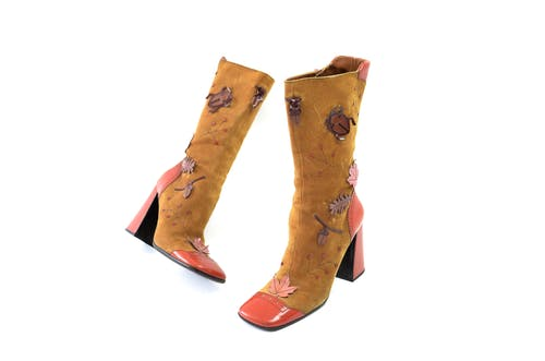 Pair of vintage suede brown boots with leather heels and nose decorated with tree leaves and bugs placed on white surface