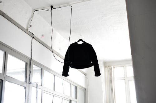 From below of simple black sweater hanged on ceiling in white room with glass windows