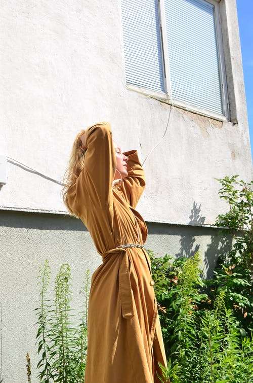Stylish woman standing near apartment building
