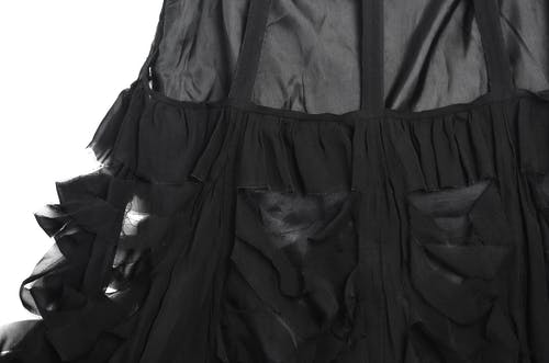 Part of skirt from silk with creative thin ruffles on white background in studio