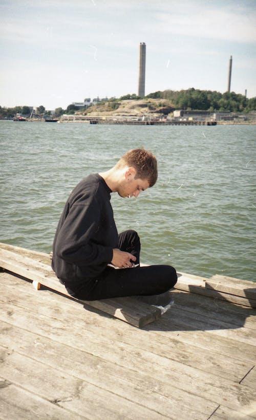 Kahverengi Ahşap Iskele üzerinde Oturan Siyah Uzun Kollu Gömlekli Adam