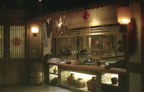 Interior of oriental restaurant with wooden door near counter and dim illumination from lamps