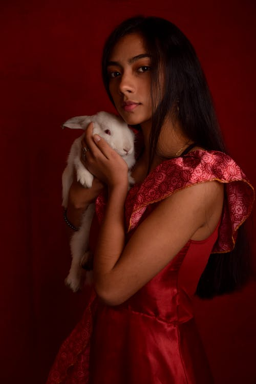 Woman in Red Dress Carrying White Puppy