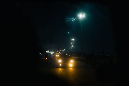 Through windshield glass of various cars with glowing headlights driving on asphalt road in city against dark night sky