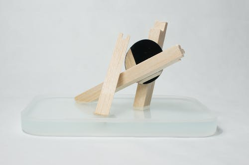 Wooden artwork on glass stand in studio
