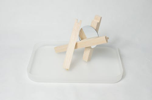 High angle of wooden sticks with mirror placed on glass stand against white background