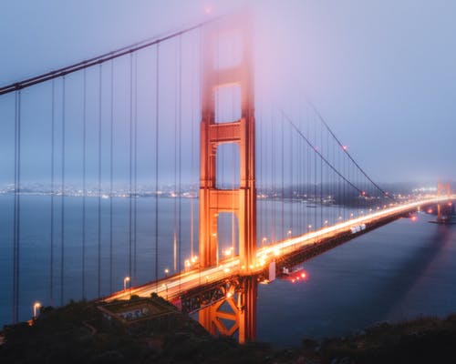 Long exposure of famous suspension Golden Gate Bridge with glowing lights crossing calm river in dusky time with fog in San Francisco