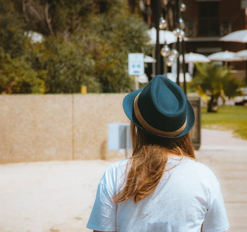 Woman in White Shirt and Blue Fedora Hat Standing on Road