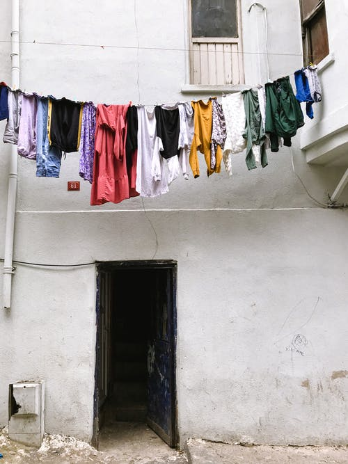 Assorted Clothes Hanged on White Wall