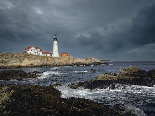 Lighthouse on rocky coastline near splashing sea