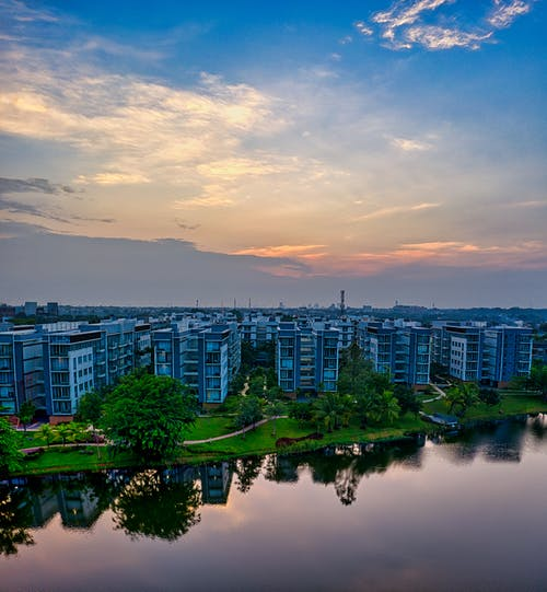 Multistory dwelling houses located near embankment of river covered with green plants at sunset