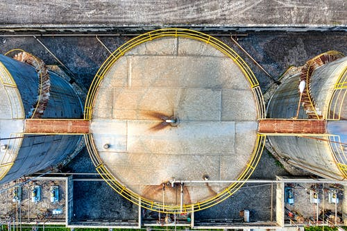 Top view of huge industrial tanks connected with rusty passages located at territory of factory
