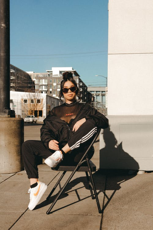 Confident young ethnic female chilling on street on sunny day
