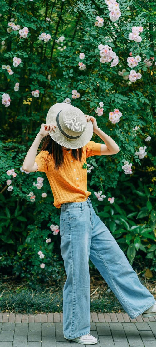 Woman in Yellow Sleeveless Shirt and Blue Denim Jeans Wearing White Hat Standing Beside Pink Flowers