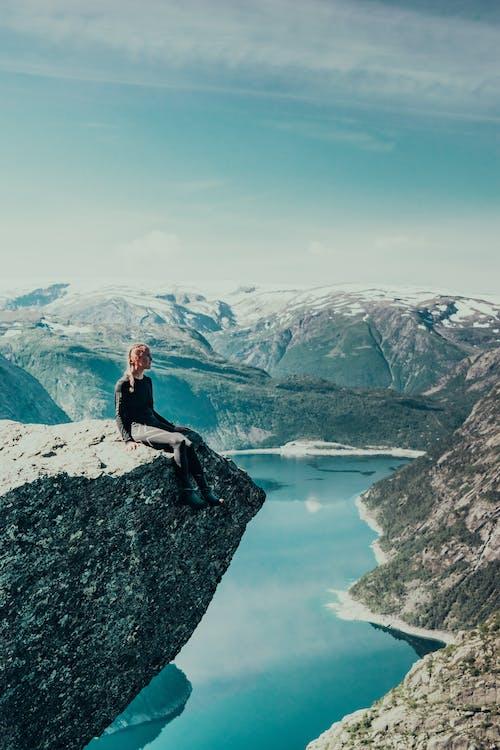 Woman in Black Jacket Sitting on Rock Formation Near Lake