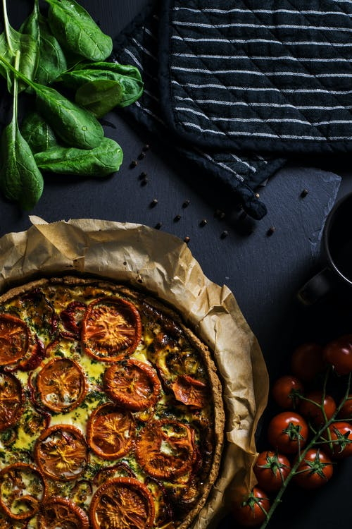 Pizza With Tomatoes on Black Surface