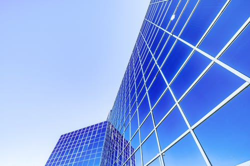 Low angle of modern high rise skyscraper with glass walls placed in city under cloudless blue sky in sunny day