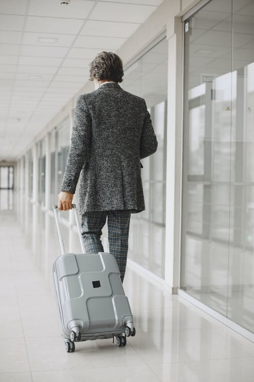 Back View of a Man in a Gray Suit Walking with His Luggage