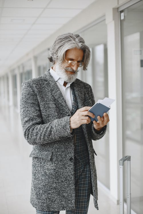 Photo of a Man with Gray Hair Looking at His Passport