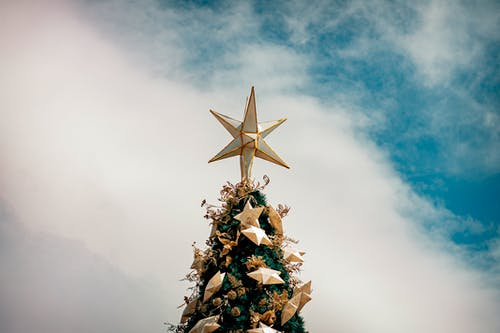From below Christmas tree edge with golden star on top and decorative baubles against sunny blue sky
