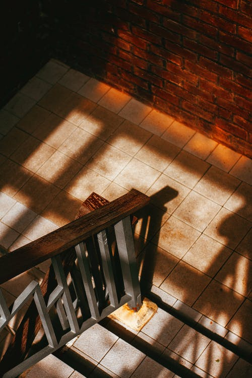 High angle of tiled stairway with wooden and metal railing in house with brick walls in sunlight